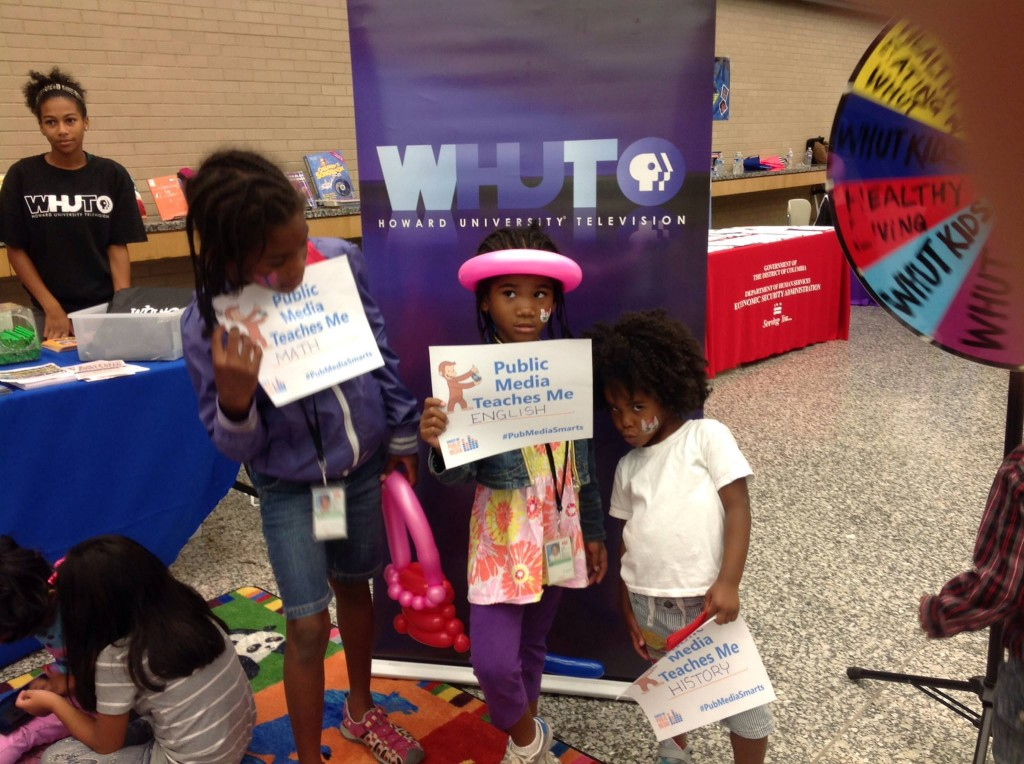 Sisters pose with their postcards at a WHUT event.