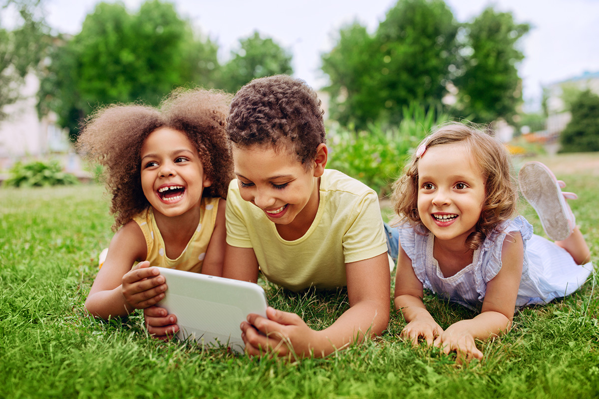 Happy children holding a tablet outside